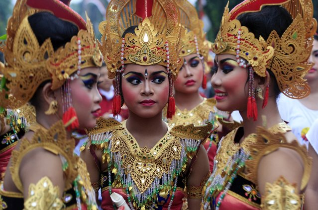 Balinese girls in traditional costumes gather during a parade for this year's last sundown in Bali island, Indonesia on New Year's Eve, Tuesday, December 31, 2013. (Photo by Firdia Lisnawati/AP Photo)