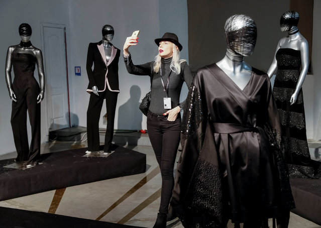A visitor takes a selfie at an exhibition of creations by Ukrainian designer Sergey Ermakov during Ukrainian Fashion Week in Kiev, Ukraine February 5, 2019. (Photo by Gleb Garanich/Reuters)