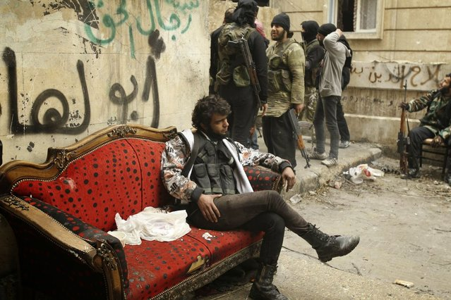 "A ""Free Syrian Army"" fighter rests on a red couch in Jeb Chalabi neighborhood, West Aleppo December 31, 2013. (Photo by Ammar Abdullah/Reuters)"