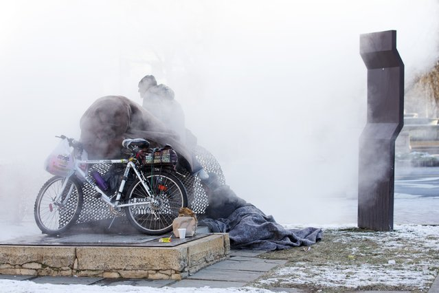 Steam swirls in frigid air as Nick, bottom right, and three homeless men who declined to give their names, keep warm by a steam grate by the Federal Trade Commission, just blocks from the Capitol, during below freezing temperatures in Washington, Saturday, January 4, 2014. (Photo by Jacquelyn Martin/AP Photo)