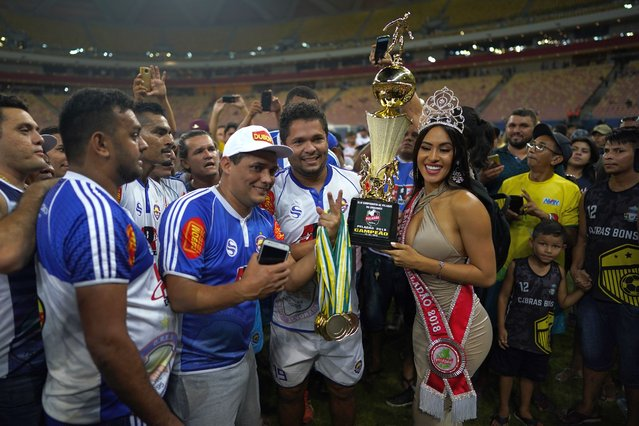 Alvorada soccer team players and staff pose with beauty Queen Isabelle Nogueira who holds their trophy after winning the Peladao amateur soccer tournament final at Arena da Amazonia in Manaus, Brazil, on Saturday, February 16, 2019. All men's teams must have a candidate for queen of the Peladao, and if the woman they chose for some reason abandons the bid before she has been disqualified, her team is removed from contention. (Photo by Victor R. Caivano/AP Photo)