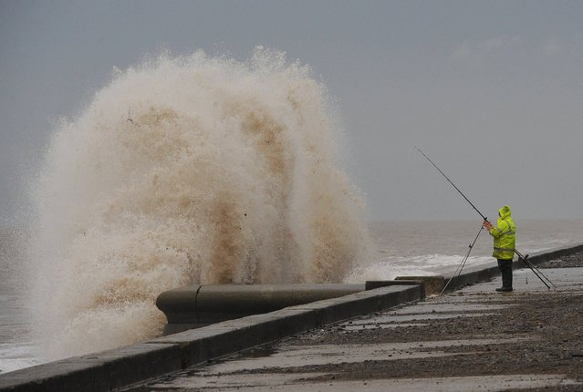 A man fishing braves the wind and rough sea at Cleveleys, Lancashire as stormy weather continues across parts of the country, on  January 5, 2014. (Photo by Anna Gowthorpe/PA Wire)