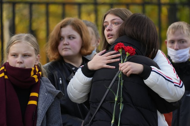 Students comfort each other as they gather outside the Perm State University following a campus shooting in Perm, about 1,100 kilometers (700 miles) east of Moscow, Russia, Tuesday, September 21, 2021. A student opened fire at the university, leaving a number of people dead and injured, before being shot in a crossfire with police and detained. Beyond saying that he was a student, authorities offered no further information on his identity or a possible motive. (Photo by Dmitri Lovetsky/AP Photo)
