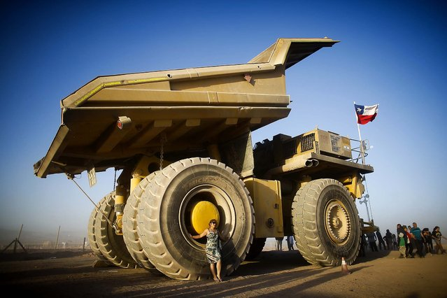 A woman poses next to a giant mining truck at the entrance of the Dakar Rally camp in Calama, Chile. The truck operates in copper mines near the city. (Photo by Victor R. Caivano/Associated Press)