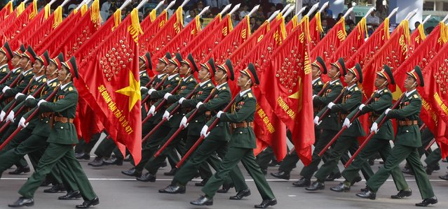 Vietnamese military soldiers carry flags with medals while marching during a rehearsal for a military parade as part of the 40th anniversary of the fall of Saigon in southern Ho Chi Minh City (formerly Saigon City), Vietnam, on April 26, 2015. (Photo by Reuters/Kham)