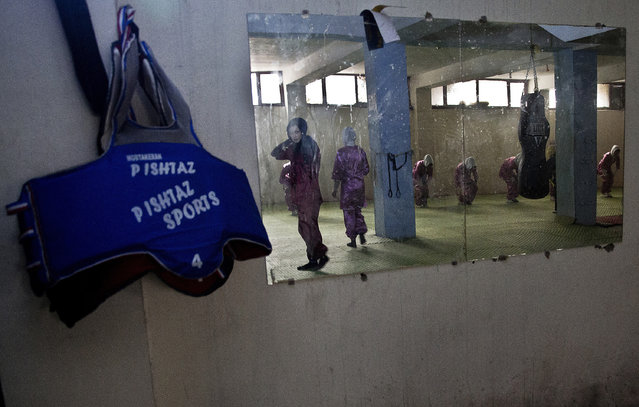 In this reflection Shaolin martial arts students train at their club in Kabul, Afghanistan, Tuesday, January 25, 2017. When they aren't training on the snow covered hills that surround Kabul, the students train in a grungy, dark club financed by a young cinema actor. (Photo by Massoud Hossaini/AP Photos)
