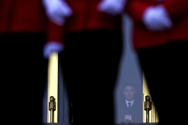 A soldier dressed as an usher watches Chinese bus ushers taking photos on the steps of the Great Hall of the People during the closing session of the Chinese People's Political Consultative Conference (CPPCC) in Beijing, Monday, March 14, 2016. (Photo by Andy Wong/AP Photo)