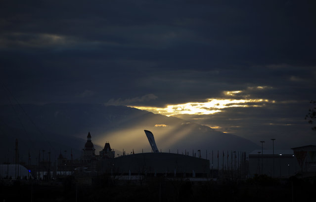 The sun rises over the Olympic cauldron in the Olympic Park at the 2014 Winter Olympics, Wednesday, February 5, 2014, in Sochi, Russia. (Photo by David Goldman/AP Photo)