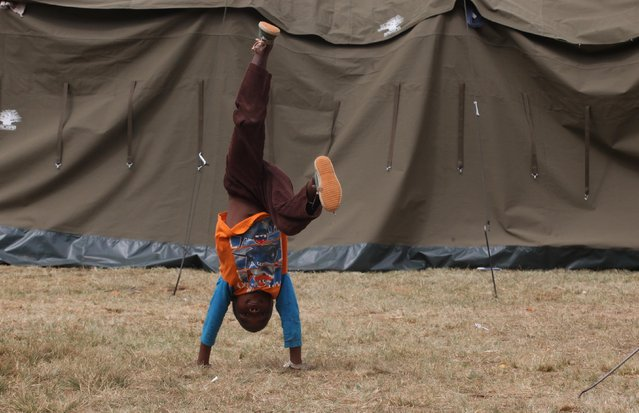A child does a handstand outside a tent at a shelter for victims of immigrant attacks in Johannesburg, Wednesday, April 22, 2015. (Photo by Denis Farrell/AP Photo)