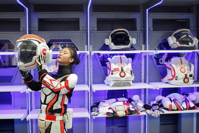 A staff member demonstrates how she puts on the helmet of a mock space suit at the C-Space Project Mars simulation base in the Gobi Desert outside Jinchang, Gansu Province, China, April 17, 2019. The facility – comprising several interconnected modules including a greenhouse and a mock decompression chamber – opened its doors to the public. (Photo by Thomas Peter/Reuters)