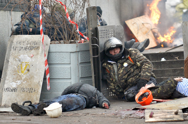An anti-government protester sits near the bodies of two demonstrators killed by a sniper during clashes with the police in the center of Kiev, on February 20, 2014. (Photo by Sergei Supinsky/AFP Photo)