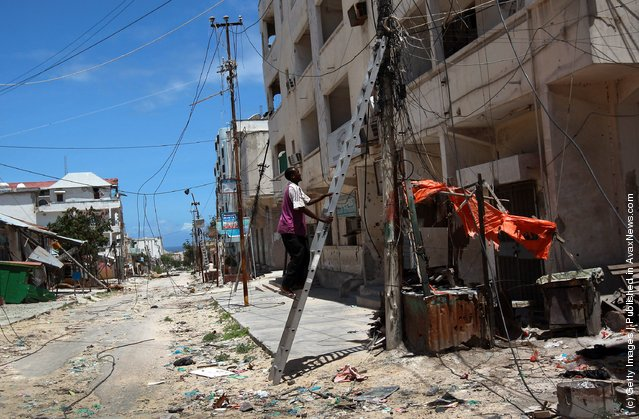 A Mogadishu municipal electrician climbs to inspect jumbled power connections in the Bakara market