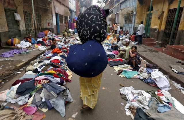 Ratana Das, 40, a female vendor, carries sacks full of clothes at a second-hand clothing market early morning in Kolkata, India, March 10, 2016. Das said she was born and brought up in Kolkata and feels proud being a resident of the city that gives her he opportunity to be financially independent. (Photo by Rupak De Chowdhuri/Reuters)