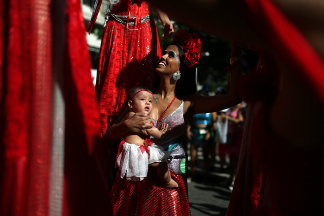 A reveller carrying her baby takes part in the annual block party Cordao do Boitata during pre-carnival festivities in Rio Janeiro, Brazil February 19, 2017. (Photo by Pilar Olivares/Reuters)
