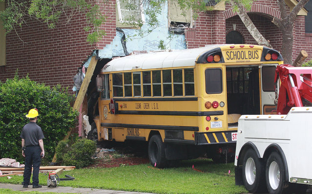 A Clear Creek Independent School District school bus is pulled out of a house it crashed into in the Oaks of Clear Creek neighborhood in League City, Texas, Tuesday, May 12, 2015. The driver, an aide, and an 11-year-old student were on board at the time of the crash and were all transported to the hospital with minor injuries. (Photo by Kevin M. Cox/AP Photo/The Galveston County Daily News)