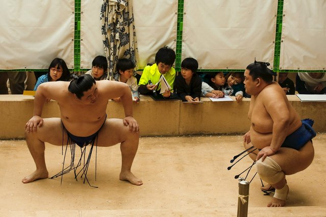 "Children watch sumo wrestlers warm up before the ""Honozumo"" ceremonial sumo tournament at the Yasukuni Shrine in Tokyo April 3, 2015. (Photo by Thomas Peter/Reuters)"