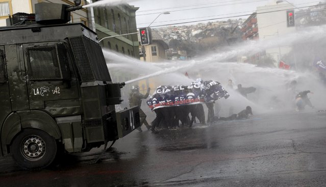 Demonstrators are hit by jets of water released by riot police vehicles during a rally, as Chile's President Michelle Bachelet delivers a speech inside the National Congress, in Valparaiso city, May 21, 2015. (Photo by Carlos Vera/Reuters)
