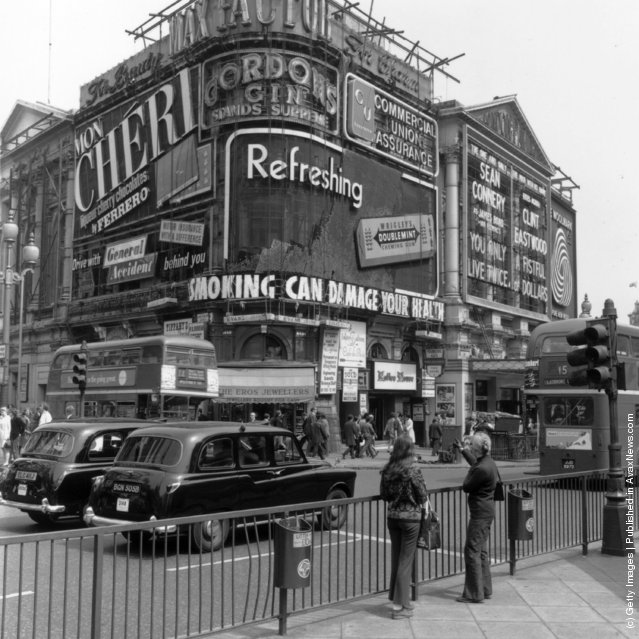 1971: Two girls pointing at the signs in Piccadilly circus, London, which include an advertisement for Wrigley's Chewing gum and a Government health warning about smoking