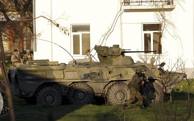 An armoured vehicle and armed people are seen in the territory of a military base after an assault of pro-Russian forces in the Crimean town of Belbek near Sevastopol March 22, 2014. (Photo by Vasily Fedosenko/Reuters)