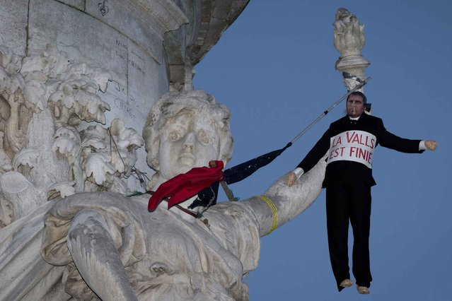 """This picture taken on April 10, 2016 shows a dummy representing French Prime Minister Manuel Valls hanged to the """"Statue of the Republic"""" during the """"Nuit Debout"""" (Up All Night) movement on the Place de la Republique in Paris. The banner reads : """"The waltz is over"""", a word play associating the name of Manuel Valls and the waltz dance, written """"valse"""" in French. In the heady new world of """"Up All Night"""" it was March 41 on Sunday to the people gathered in a main Paris square to share their aspirations for change. (Photo by Joel Saget/AFP Photo)"""