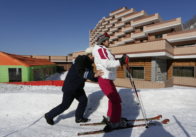 """A staff helps a North Korean woman to ski at Masik Pass ski resort, North Korea, February 22, 2014. North Korea's newest symbol of national pride and """"single-minded unity"""", the ski resort at Masik Pass, nestled deep in North Korea's eastern mountains, is an impressive site. It has 10 ski runs, from beginning to advanced, a well-equipped rental shop, and a 250-room, eight-story hotel for foreigners alongside a 150-room hotel for Koreans. (Photo by Vincent Yu/AP Photo)"""