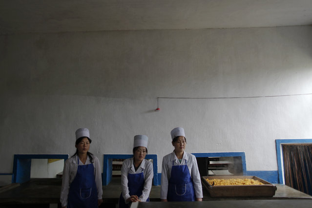 North Korean women stand by a simple meal of maize prepared for orphans in the area damaged by recent floods and typhoons in the North Hwanghae province September 29, 2011. (Photo by Damir Sagolj/Reuters)