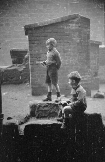 Two young boys playing with toy guns in a derelict area of the Gorbals in Glasgow on January 31, 1948. (Photo by Bert Hardy/Picture Post/Getty Images)