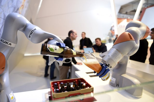 Robots in the Kuka stand pour a beer into a glass at the Hannover Messe industrial trade fair in Hanover, Germany April 23, 2016. (Photo by Nigel Treblin/Reuters)