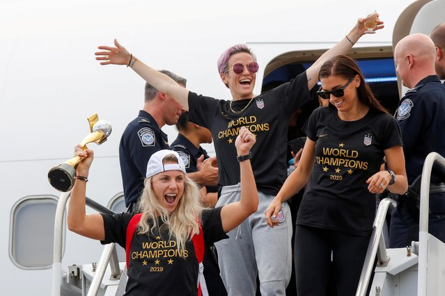 U.S. soccer players Julie Ertz (L), Megan Rapinoe (C) and Alex Morgan celebrate as they exit the plane with the Trophy for the FIFA Women's World Cup while the U.S team arrive at the Newark International Airport, in Newark, New Jersey, U.S., July 08, 2019. (Photo by Eduardo Munoz/Reuters)