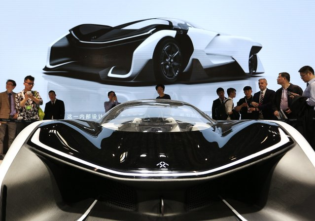 Visitors look at Faraday Future's single-seat concept car FFZero1at Auto China 2016 motor show in Beijing, China, 25 April 2016. The 14th Beijing International Automotive exhibition or Auto China 2016 will run from 25 April to 04 May 2016. (Photo by How Hwee Young/EPA)