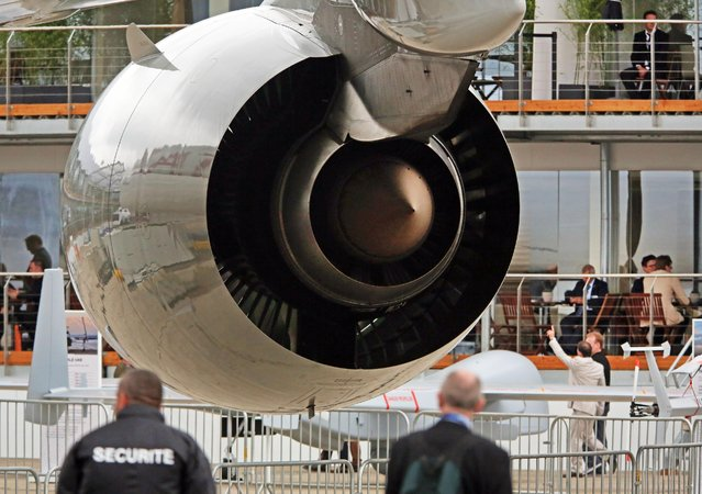 Visitors walk next to the Rolls Royce jet engine of a Qatar Airways Airbus A 380, at the Paris Air Show in Le Bourget, north of Paris, Thursday June 18, 2015. Some 300,000 aviation professionals and spectators are expected at this week's Paris Air Show, coming from around the world to make business deals and see dramatic displays of aeronautic prowess and the latest air and space technology. (AP Photo/Remy de la Mauviniere)