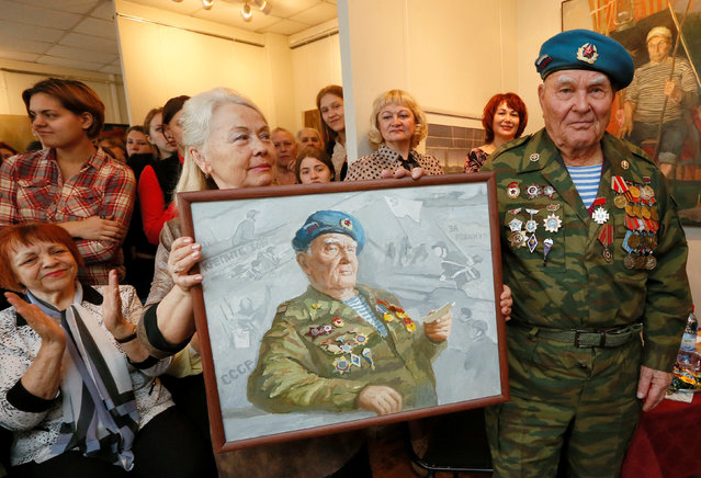 Georgy Ivkin, 91, former airborne troops soldier and World War Two veteran, stands near an oil painting, a portrait of himself created by a student of Krasnoyarsk Art College as a present for the upcoming Victory Day, during a meeting in Krasnoyarsk, Siberia, Russia, April 28, 2016. (Photo by Ilya Naymushin/Reuters)