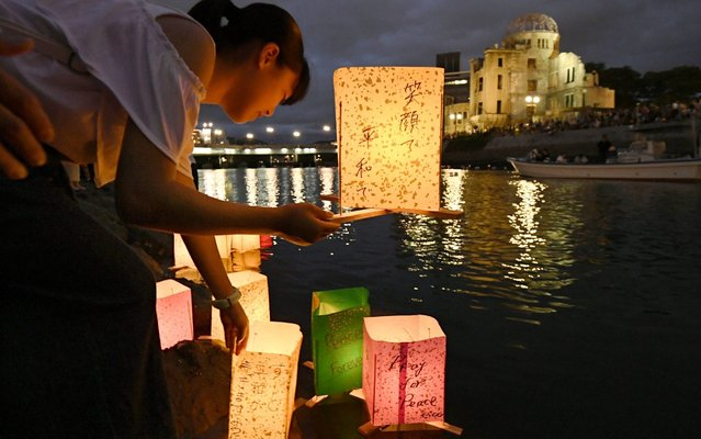A girl floats a lantern on Motoyasu River in Hiroshima, western Japan, on August 6, 2019, in memory of victims of the atomic bombing of the city, on its 74th anniversary. (Photo by Kyodo News via Getty Images)
