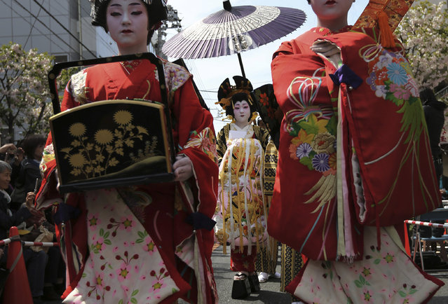 A woman, center, in authentic costumes, enacts Oiran, or high-class courtesans during the Edo period (1600 – 1868), as she takes part in an annual procession at Asakusa in Tokyo, Saturday, April 12, 2014. (Photo by Eugene Hoshiko/AP Photo)