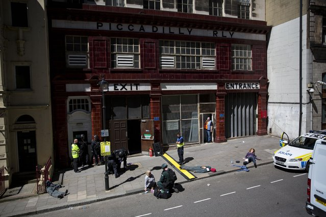 People take part in a training exercise for London's emergency services outside the disused Aldwych underground train station in London, Tuesday, June 30, 2015. (Photo by Matt Dunham/AP Photo)