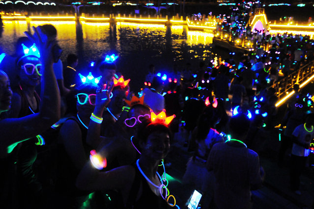 A special parade featuring colorful illuminations was held on Wednesday (1 July 2015) night in the southern Chinese city of Fangchenggang to celebrate the 94th anniversary of the founding of the Communist Party of China (CPC). Thousands of local residents put on illuminous decorations to light up the event of jogging or skipping for 15km. (Photo by Imaginechina/Splash News)
