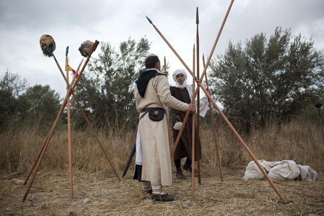 In this Thursday, July 2, 2015 photo, Israeli and Russian members of knight clubs build their camp before marching 27 kilometers (17 miles) to the reenactment of the Battle of Hattin from the ancient northern city of Zippori to Horns of Hattin, northern Israel. (Photo by Oded Balilty/AP Photo)