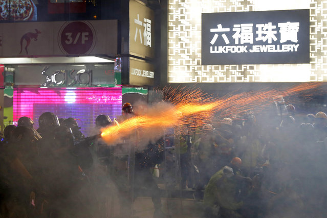 Policemen fire tear gas shells toward protestors at a shopping district of Hong Kong, Saturday, August 31, 2019. Many of the protesters outside Hong Kong government headquarters have retreated as large contingents of police arrive on the streets in what looks like preparation for a clearing operation. (Photo by Kin Cheung/AP Photo)