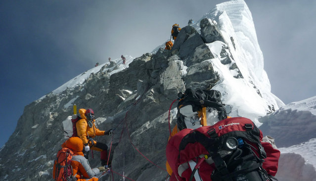 """In this May 19, 2009 file photograph, unidentified mountaineers walk past the Hillary Step while pushing for the summit of Mount Everest as they climb the south face from Nepal. A group of top Nepalese climbers is planning a high-risk expedition to clean up Everest, saying decades of mountaineering have taken their toll on the world's highest peak. """"Everest is losing her beauty"""", seven times Everest summitteer Namgyal Sherpa, 30, told AFP. """"The top of the mountain is now littered with oxygen bottles, old prayer flags, ropes, and old tents. At least two dead bodies have been lying there for years now"""". (Photo by Courtesy of Pemba Dorje Sherpa/AFP Photo)"""