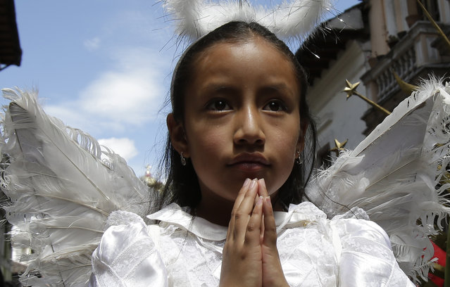 In this June 14, 2015 photo, a girl dressed as angel parades with her hands folded in prayer during a procession marking Ecuador's identity as a Catholic nation with its 1874 consecration to the Sacred Heart of Jesus, in Quito. Although eight of 10 people in Ecuador say they are Catholic, many take part in festivals that feature joyous dances and ceremonial acts of thanks to the ancient native gods. (Photo by Dolores Ochoa/AP Photo)