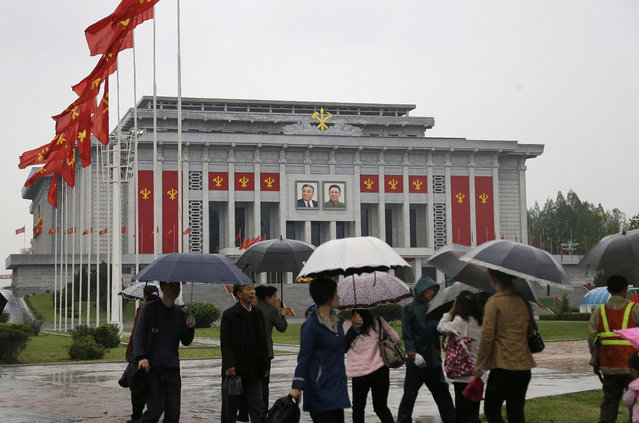 North Koreans carry umbrellas as they walk past the April 25 House of Culture, decorated in the colors and flags of their ruling party, the Workers' Party on Thursday, May 5, 2016, in Pyongyang, North Korea. Members of North Korea's ruling party have gathered in Pyongyang ahead of their biggest political conference in decades. Foreign experts say North Korea's leader Kim Jong Un will likely use the meeting to place his loyalists into key positions, strengthen his push to upgrade his country's nuclear arsenal and cement his grip on power. (Photo by Wong Maye-E/AP Photo)