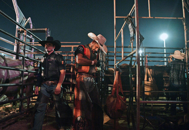 Riders prepare before competing at a rodeo event in Monte Negro, south of the Amazon basin, Rondonia state, Brazil on August 30, 2019. (Photo by Carl De Souza/AFP Photo)