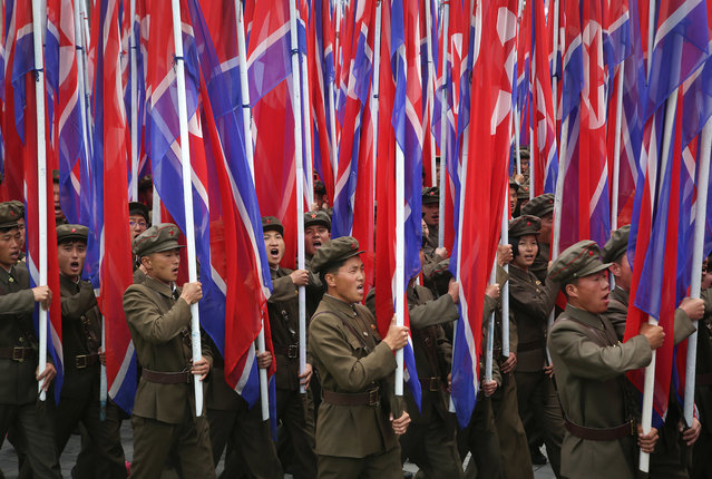 Parade participants carry the North Korean flag as they march on Kim Il Sung Square on Tuesday, May 10, 2016, in Pyongyang, North Korea. (Photo by Wong Maye-E/AP Photo)