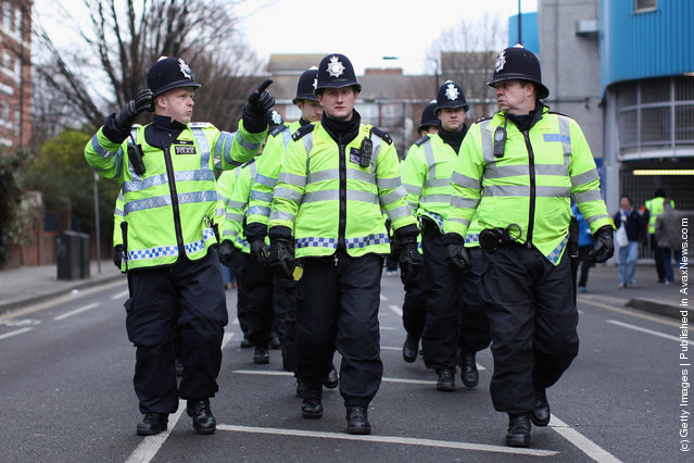 QPolice officers make there way past the Loftus Road stadium as searches are made of football fans prior to the FA Cup Fourth Round between Queens Park Rangers and Chelsea