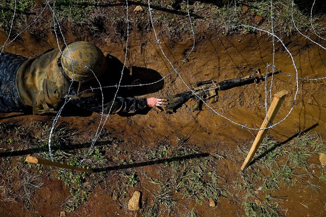 A member of the United States Naval Academy freshman class pushes a fake-gun through trenches at the wet and sandy station during the annual Sea Trials training exercise at the U.S. Naval Academy on May 13, 2014 in Annapolis, Maryland. (Photo by Patrick Smith/Getty Images)