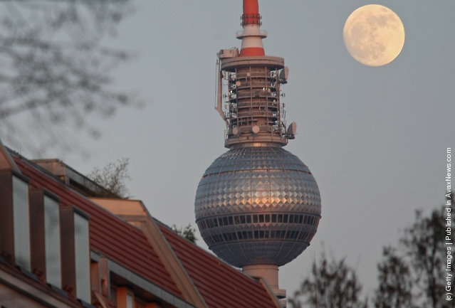 The full moon rises behind the television tower and trees with bare branches in Berlin, Germany