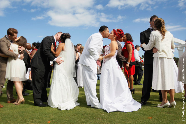 (L-R) Jonah Klemm-Toole kisses his new wife, Elena Pizano, Kenny Dornhoefer kisses his new wife, Jaya Ganaishalm and Manuel Fuentes kisses his new wife, Monika Juarbe after being wed during a group Valentine's day wedding at the National Croquet Center