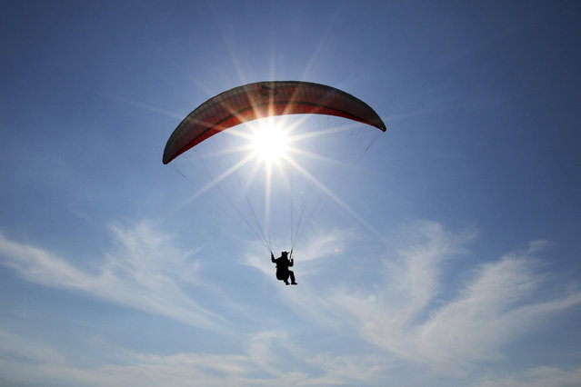 A paraglider flies during the annual Balkan paragliding competition over the city of Vlore, some 150 km (94 miles) from Tirana, May 7, 2014. (Photo by Arben Celi/Reuters)