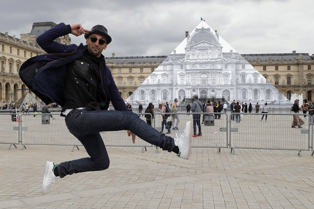 Street artist JR poses in front the Louvre Pyramid in Paris, Tuesday, May 24, 2016. (Photo by Francois Mori/AP Photo)