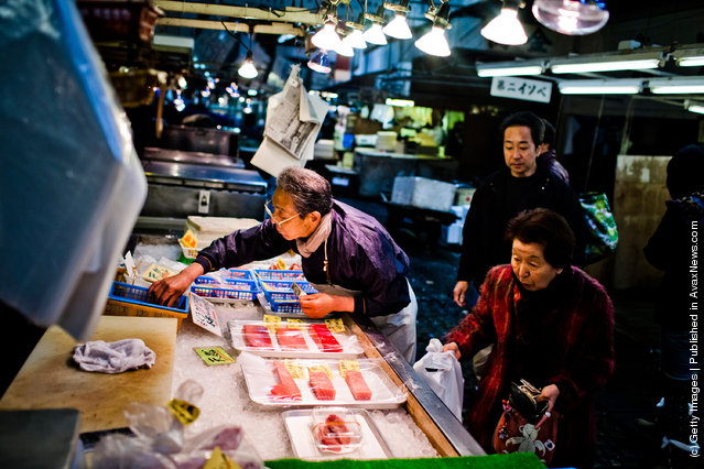 A worker looks for change as he serves a customer at the Tsukiji fish market